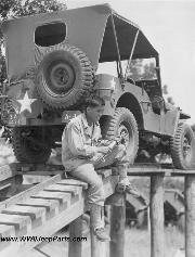 Here a member of the 442nd combat team prepares to go into action with the grease gun on one of the now familiar and famous jeeps at Camp Shelby, Mississippi. 7/1943.