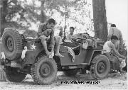 Members of the 442nd combat team drape themselves on a jeep to dress after a cool swim in the Leaf River near Camp Shelby, Mississippi, 7/1943.