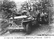 Members of the 442nd RCT advance in the Chambois Sector, France. Notice antidecapitation device, tow rope, M1917 watercooled .30cal machine gun on M-48 dash mount, unusual rifle rack location, windshield cover, and jeep trailer.