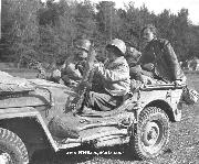 Two soldiers of the 442nd RCT are in a Jeep accompanied by two French guides in October 1944 in the Chambois Sector, France, Notice unusual mounting of metal rifle holder and hand pick through side grab handle  as well as Machine Gun Dash Mount.