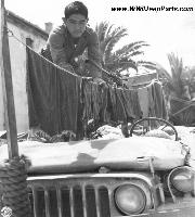 A soldier of the 442nd RCT hangs his laundry on a jeep so it won't be lost during a sudden move in Castellina Sector, Italy on 12 July 1944. Notice anti-decapitation device, tow rope, and windshield cover.