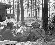 Two Airborne soldiers in the Oosterbeek pocket with Sten guns. The man on the left is a signaller as he wears a set of headphones connected to the Jeep above him, containing a longer-ranged Type 22 set. An Airborne Trailer in the distance.