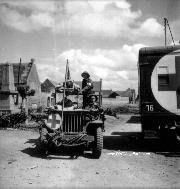 Wounded soldiers are transported on a stretcher-carrier jeep ambulance by members of the 23d Field Ambulance RCAMC assigned to the 9th Infantry Brigade, 3rd Canadian Infantry Division, Basly, France, June 27, 1944.