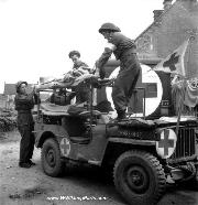Wounded soldiers are helped from a stretcher-carrier jeep ambulance by members of the 23d Field Ambulance RCAMC assigned to the 9th Infantry Brigade, 3rd Canadian Infantry Division, Basly, France, June 27, 1944.