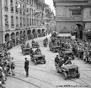 Police offiers in Willys Jeeps and sidecar motorcycles of the Swiss army lead the convoy of guests to a post-war reception of the Princess and Prince of the Netherlands in the old town of Bern.