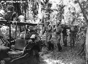 U. S. Soldiers Evacuating Wounded From Jungle in 1943. US soldiers on the New Georgia Islands carry a wounded comrade on a stretcher, while another wounded soldier lies on top of a jeep.