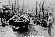 Medics of the 10th Mountain Division evacuating wounded in a jeep while tanks wait to use the one-lane road, April 1945
