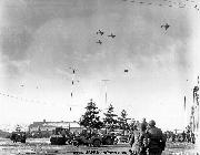 Soldiers watch a Bastogne supply drop surrounded by a wide variety of jeeps.