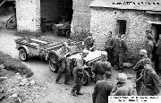 Fallschirmj�ger inspect a captured American Jeep and trailer. A German amphibious Volkswagen Schwimmwagen is parked in the background. St. Lo area, Normandy, France, Summer 1944.