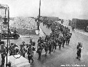 Columns of GI's march past jeeps as they move off the beaches of Normandy, France on D-Day. A Censor has blotted out building tops to prevent the determination of the exact location of the troop movements.