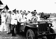Franklin D. Roosevelt Greeting Military Personnel from inside a jeep.