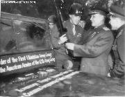 General Omar Bradley, commander of the U.S. 12th Army Group, presents an American carbine and jeep to Marshal Ivan Konev of the Russian army following a banquet celebrating victories of their troops near Berlin, Germany. 1945.