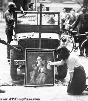Parisians show what they'd like to do with Hitler: Two French partisans deface a portrait of Hitler propped up againt a jeeps front bumper. They were part of the vast throng which turned out for the victory parade honoring the liberators of the French capital.