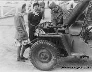 Two young evacuees of Japanese ancestry watch an army mechanic repair an early Jeep at Santa Anita assembly center, Arcadia, California. 4/6/1942