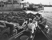 A barge loaded with jeeps is steered towards a cargo ship during World War II. Notice Ax and Shovels.
