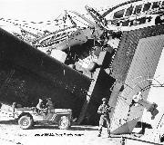 A U.S. army soldier with a sub-machine gun and another in a jeep guard the looming S. S. Partos which was damaged and had capsized against the dock when the Allies landed at the North African port, in 1942. Notice fender mounted decontaminator.