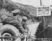 Officers in a jeep read a sign directing Rubbernecks About Turn - You hinder the men at the front.