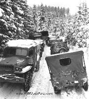 Jeeps and trucks lined up on a snowy forest road. Deep snow banks on a narrow road halt military traffic in the woods of Wallerode, Belgium January 30, 1945.