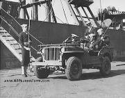 A Coast Guard officer is shown at an East coast port with armed Coast Guardsmen in a jeep as he inspects the vigilant waterfront patrols that guard vital war supplies being shipped across. Valuable shipping must be protected on the piers as well as on the shipping lanes. April, 1943