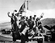 Marines on Iwo Jima celebrate the War is over by crowding on a Ford GPW Jeep with musical instruments..