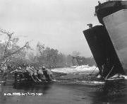 A Jeep from a Coast Guard-manned LST (Landing Ship Tank) being pushed ashore through the surf at Cape Gloucester, New Britain, by Coast Guard and Marines, December 26, 1943.