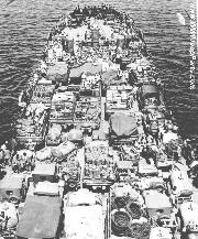 LST loaded with many Jeeps and water buffalo trailers. Coast Guard LST lands Marines during Cape Gloucester, New Britain invasion. December 24, 1943.