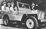 Admiral Chester William Nimitz, the Commander-in-Chief of the US Pacific Fleet, takes a ride around Pearl Harbor with his aides-de-camp in a jeep presented to the fleet by the US Army in honour of their naval victory at Midway Island. The former army jeep is painted battleship grey. 1942
