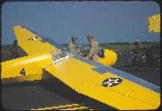 An Olive Drab painted USN jeep with yellow markings provides a tow for a U.S. Marine glider at Page Field, Parris Island, S.C. in May 1942.