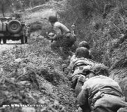 American soldiers leave their jeep in the road when they come under fire from German mortar and machine guns. July 1, 1944.