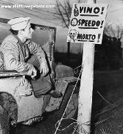 December 23, 1943 Soldier in jeep looking at sign in Italy. Vino! Speedo! Morto! Translated into English this Italian sign means Wine, Speed! Death!