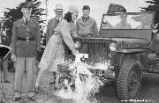 Willys Slatgrill MB Jeep Dedication - Nina Bissell of Women's Auxiliary State Guard breaks bottle across jeep bumper in ceremony at University of San Francisco. Watching are (L to R) Lt. Col. Englehart, Mayor Rossi, Lt. Clay. Students purchased enough stamps and bonds to pay for twenty jeeps. Apr 8, 1942.