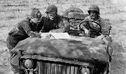 American soldiers use the front of a Willys Slatgrill MB jeep as a table on which to examine plans for further advances in Algeria.