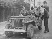 A very early Willys Slatgrill MB in England. Notice very early shovel. Also notice Driver's fender top was never drilled for Blackout Driving Lamp Bracket, the single windshield wiper, the rubber hood blocks, and solid black steering wheel. British Black Out Modifications include: UK version of Blackout Driving Light in front of grill, white painted front bumper, and painted over headlights.