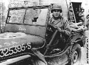 Major General Maxwell Davenport Taylor, commander of the 101st Airborne Division, behind the wheel of a jeep in France 1945. Notice D-Day Invasion Windshield Paper Label Flag, Leather Rifle Scabbard, and Tow Rope