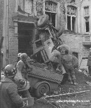 A WWII Jeep Trailer 1/2 buried while still attached to the towing vehicle - a flipped Dodge - after a German Artillery Attack.
