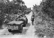 77th Army Division marches to the front at Yigo along road slashed through jungle vegetation of northern Guam. Men, jeeps and tanks make up the procession. 8/31/1944